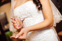Braut hält Parfüm in der Hand und spritzt auf Handgelenk Lizenzfreie Stockfotos