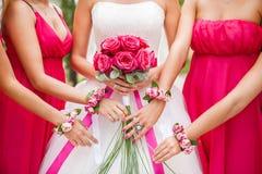 Braut hält Rosarosenblumenstrauß in den Händen brautjunfer lizenzfreie stockbilder