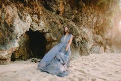 Braut im blauen Hochzeitskleid im Strand an den Sonnenuntergang- oder Sonnenaufgangfarben Blonde Frau des Art und Weisebaumusters Lizenzfreie Stockfotos
