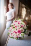 Braut im Fensterrahmen und Hochzeitsblumenstrauß im Vordergrund Hochzeitsblumenstrauß mit einer Frau im Hochzeitskleid im Hinterg Stockfoto