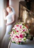 Braut im Fensterrahmen und Hochzeitsblumenstrauß im Vordergrund Hochzeitsblumenstrauß mit einer Frau im Hochzeitskleid im Hinterg Stockfotografie