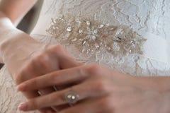 Braut im Guipurespitzenkleid und in einer Brosche an der Taille, Nahaufnahme stockbild
