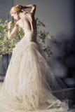 Braut im Hochzeitskleid hinter Busch mit Blumen Lizenzfreie Stockbilder