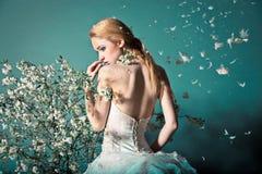 Braut im Hochzeitskleid hinter Busch mit Blumen Stockfotografie