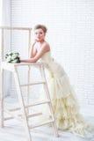 Braut im Hochzeitskleid mit Blumen und Treppenhaus Stockfotos