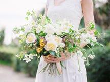 Braut im Hochzeitskleid mit Blumenstrauß Blonde Frau des Art und Weisebaumusters im bräutlichen weißen Kleid mit Regenschirm Stockbild