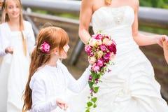 Braut im Hochzeitskleid mit Brautjungfern auf Brücke Stockfotos