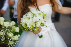 Braut im Kleid hält Brautblumenstrauß mit Freesie lizenzfreie stockbilder