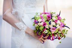 Braut im Kleid und im Brautschleier hält Hochzeits-Blumenstrauß stockfotos