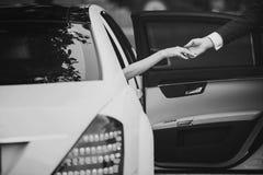 Braut im Luxusauto gibt dem Bräutigam Hand lizenzfreie stockbilder