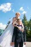 Braut im Park umarmt den Bräutigam im Hochzeitstag Lizenzfreies Stockbild