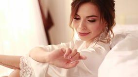 Braut im peignoir sitzt und sieht ihren Goldring mit Diamanten im Schlafzimmer an stock video