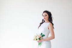 Braut im weißen Hochzeitskleid mit einem Blumenstrauß von Blumen Stockfotos