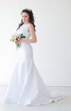 Braut im weißen Hochzeitskleid mit einem Blumenstrauß von Blumen Stockfoto