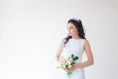 Braut im weißen Hochzeitskleid mit einem Blumenstrauß von Blumen Stockfotografie