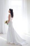 Braut im weißen Hochzeitskleid mit einem Blumenstrauß von Blumen Lizenzfreies Stockbild