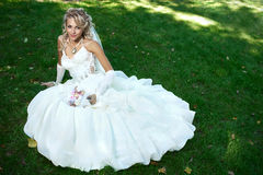 Braut im weißen Kleid auf grünem Gras Stockfotos