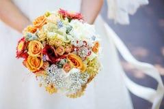 Braut im weißen Kleid, das Blumenstrauß in den Händen hält Stockfotos