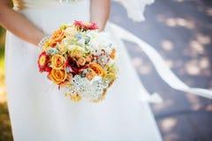 Braut im weißen Kleid, das Blumenstrauß in den Händen hält Stockfotografie