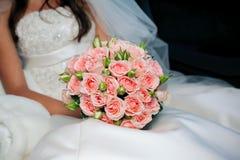Braut im weißen Kleidholdingblumenstrauß der Rosen Stockfoto