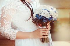 Braut im weißen Kleid, das Hochzeitsblumenstrauß hält Stockbild