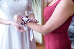 Braut kleidet Brautjungfer des Boutonniere an Hand Lizenzfreies Stockbild