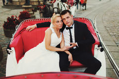 Braut lehnt sich zur Schulter des Bräutigams, die im Wagen sitzt Stockbilder