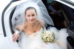 Braut mit Blumen im weißen Auto Stockfotografie