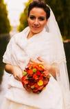 Braut mit Blumenstrauß in der weißen Pelzstola Stockfotos