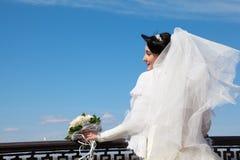 Braut mit Blumenstrauß am Geländer Lizenzfreies Stockfoto