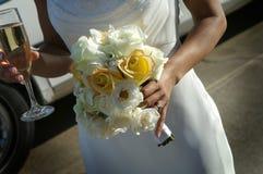 Braut mit Blumenstrauß und Champagner Stockfotos