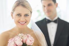 Braut mit Blumenstrauß von Rosen während Bräutigam Standing In Background Lizenzfreie Stockfotos