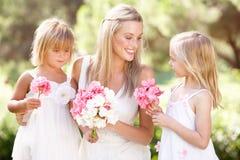 Braut mit Brautjunfern draußen an der Hochzeit Stockfotografie