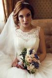 Braut mit dem dunklen Haar im luxuriösen Spitzehochzeitskleid mit Blumenstrauß von Blumen Stockfoto