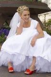 Braut mit den roten Schuhen, die auf Kandare sitzen Lizenzfreie Stockfotos