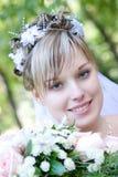 Braut mit einem Blumenblumenstrauß durch den Baum Stockfotos
