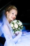 Braut mit einem Blumenblumenstrauß in einem Auto Lizenzfreies Stockfoto