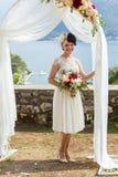 Braut mit einem Blumenstrauß am Hochzeitsbogen Lizenzfreie Stockfotos