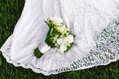 Braut mit einem Blumenstrauß der weißen Orchidee auf dem Hochzeitskleid Lizenzfreie Stockbilder