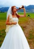 Braut mit einer Bierflasche und einem Bräutigam auf Fahrrad auf dem Hintergrund - Hochzeitskonzept Lizenzfreie Stockbilder