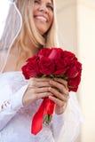 Braut mit Fokus auf ihrem roten Rosen-Blumenstrauß Lizenzfreie Stockbilder
