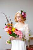 Braut mit hellem Blumenstrauß und Blumen in ihrem Haar Stockbild
