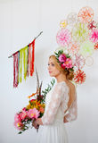 Braut mit hellem Blumenstrauß und Blumen in ihrem Haar Stockfotografie