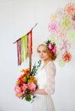 Braut mit hellem Blumenstrauß und Blumen in ihrem Haar Lizenzfreies Stockbild