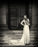 Braut mit Hochzeit blüht Blumenstrauß im weißen Kleid mit Hochzeitsfrisur und -make-up Lächelnde Frau im Hochzeitskleid WartegR lizenzfreie stockfotos