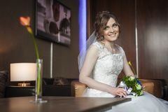 Braut mit Hochzeit blüht das Sitzen auf dem Stuhl Lizenzfreies Stockfoto