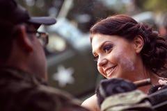 Braut mit ihrem tragenden Armeeanzug des Bräutigams Lizenzfreie Stockfotografie