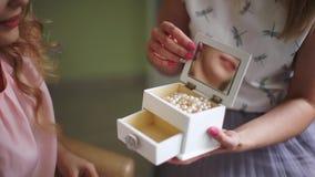 Braut mit Make-upkünstler wählt schöne Verzierungen von der Schatulle Berufsmake-up für Frau mit gesunden Jungen stock footage
