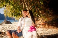 Braut mit rosa Blumenstrauß und Bräutigam auf Seil schwingen Lizenzfreie Stockbilder