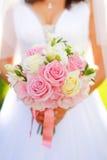 Braut mit rosafarbenem Hochzeitsblumenstrauß Stockfotos